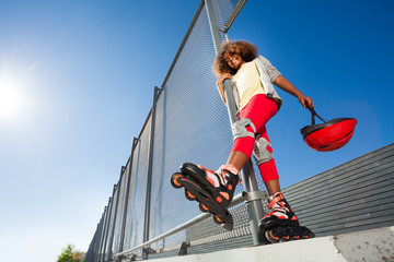 African girl in roller skates posing at skate park