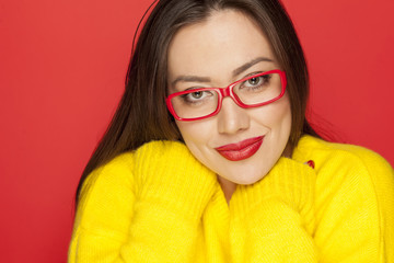 beautiful smiling woman with red glasses on red background