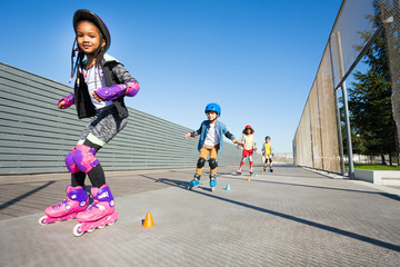 Cute African girl learning to rollerblade outdoor