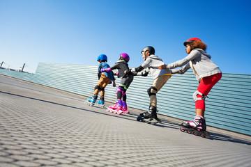 Happy preteen kids having fun while rollerblading