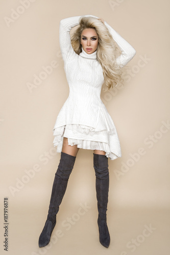 92642f7b31b Beautiful, sexy blonde woman with long hair, wearing a bright dress and long  boots