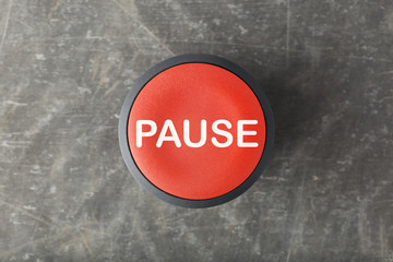 Overhead of Red Pause Push Button on Concrete Background