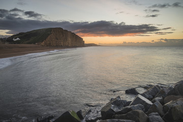 Beautiful vibrant long exposure sunrise landscape image of West Bay in Dorset England