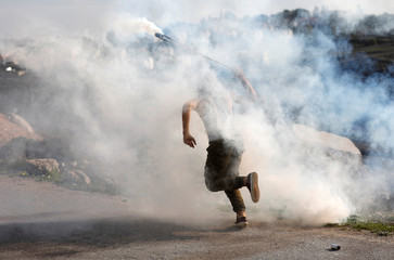 Palestinian demonstrator hurls back a tear gas canister fired by Israeli troops during clashes at a protest calling for the release of Palestinian prisoners from Israeli jails near Ramallah