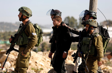 Israeli soldiers detain a Palestinian during clashes at a protest calling for the release of Palestinian prisoners from Israeli jails near Ramallah