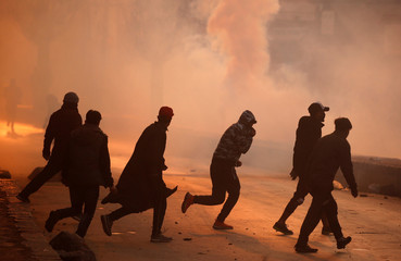 Demonstrators run amidst smoke from tear gas fired by Indian policemen during a protest in Kashmir, in Srinagar