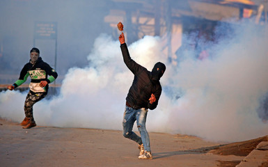 A demonstrator hurls a stone amidst smoke from tear gas fired by Indian policemen during a protest in Kashmir, in Srinagar