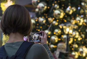 girl photographs a Christmas tree on the phone