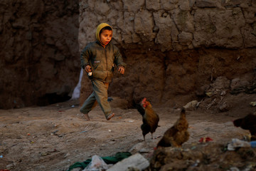 An Afghan refugee child runs in a slum in Islamabad