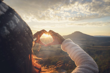 Young woman traveler making heart shape symbol at sunrise