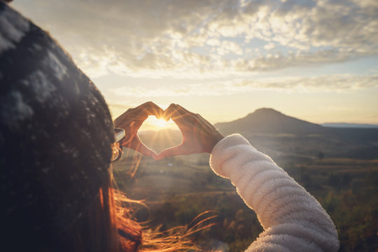 Young woman traveler making heart shape symbol at sunrise