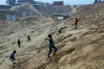 Rohingya refugee children throw stones and sand at another group of children as a game at Balukhali camp, near Cox's Bazar