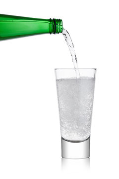 Pouring lemonade soda drink from bottle to glass