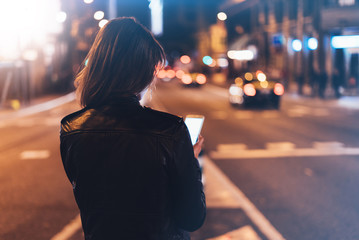 Fotomurales - Girl holding on screen smartphone on background illumination glow bokeh light in night atmospheric city, hipster girl using in hands mobile phone, lights taxi; mockup glitter street, lifestyle concept