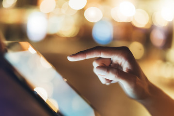 Girl texting finger on screen tablet on background bokeh light in night atmospheric city, hipster using in female hands mobile phone; mockup glitter street, content internet concept