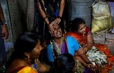 Family members mourn near the body of a victim after a ferry boat carrying schoolchildren sank in the Arabian Sea, at their residence in Dahanu
