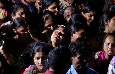 Family members mourn near the body of a victim after a ferry boat carrying schoolchildren sank in the Arabian Sea, before the funeral rituals outside their residence in Dahanu
