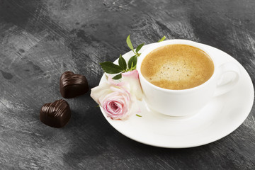 Espresso coffee in a white cup, a pink rose and chocolates on a dark background. Copy space
