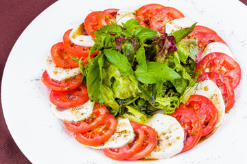 Caprese salad with spices and herbs on white plate