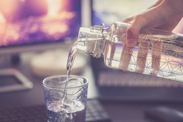 Wasser wird aus Flasche in Glas eingeschenkt, Arbeitsplatz