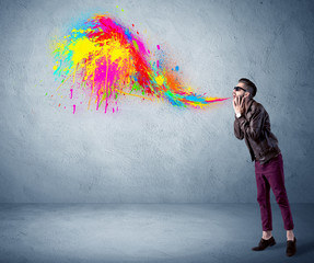 Hipster guy shouting colorful paint on wall