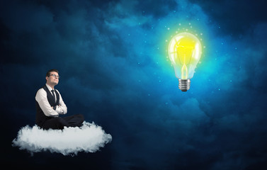 Man sitting on cloud looking at a lightbulb
