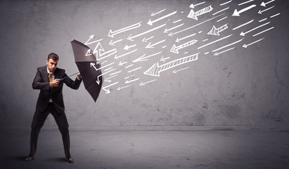 Business man standing with umbrella and drawn arrows hitting him
