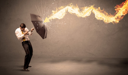 Business man defending himself from a fire arrow with an umbrella