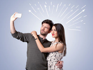 Cute couple taking selfie with arrows