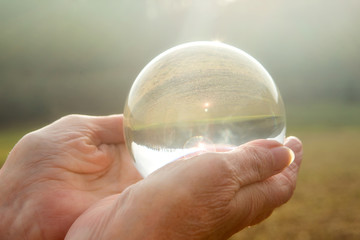 older womans hand holding a shiny glass sphere