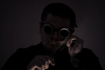 A robber with a knife. In safety glasses. A knife at the level of the head. Crime.
