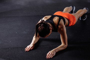 young beautiful woman in sportswear doing plank while trainnig at cross fit gym