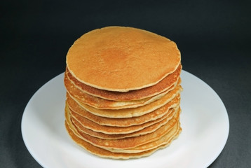 Stack of homemade plain pancakes served on white plate on black background
