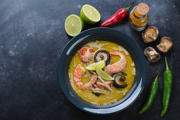 Plate of spicy thai green curry soup over dark scratched metal background, top view with copyspace, horizontal shot