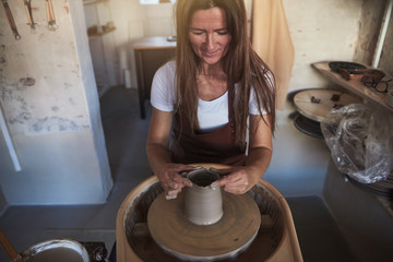Female artisan creatively sculpting wet clay on a pottery wheel