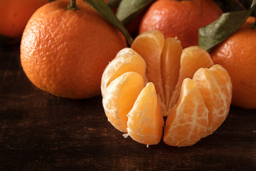 peeled clementine and whole fruits on a dark brown wooden board,  close up