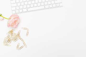 Golden paper clips and keyboard on white background. office flat lay