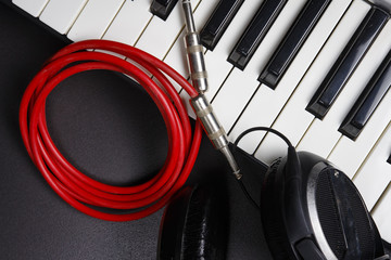 DJ Tools. Musical instruments close-up on black background. Synthesizer, headphones and cable. Midi keys and jack cable.