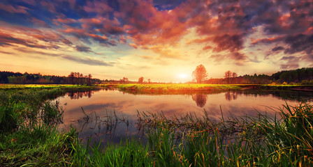Spring landscape of bright sunrise over river with colorful cloudy sky on horizon. Scenery spring nature