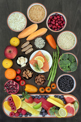 Health food for heart fitness concept with superfoods of fish fruit, vegetables, seeds, nuts, grains, cereals, spice and herbs providing high levels of omega 3 fatty acids, vitamins, and antioxidants.