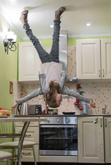 Upside down House. Little girl on the kitchen.