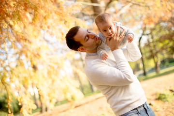 Young father and baby boy in autumn park