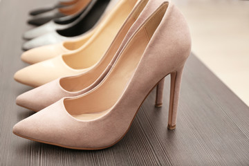 Elegant beige shoes on wooden shelf, closeup