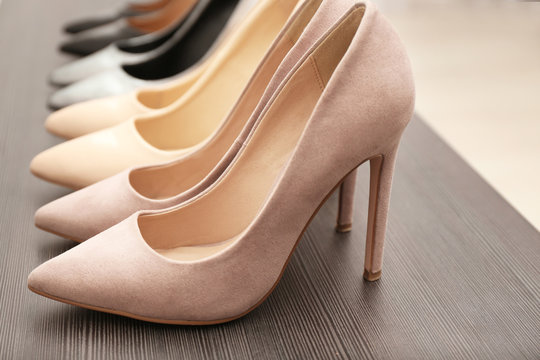 Elegant beige shoes on wooden shelf, closeup