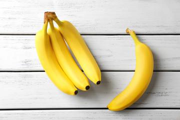 Tasty ripe bananas on white wooden background