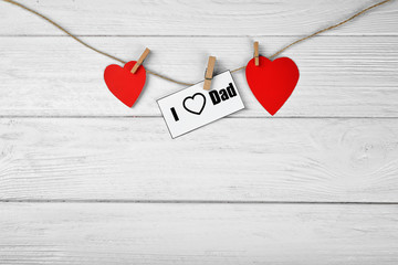 Composition with phrase I LOVE DAD for Father's Day on wooden background