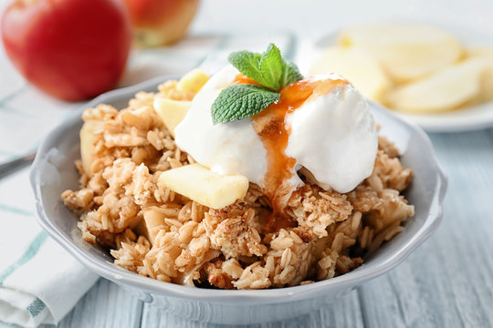 Bowl with apple crisp and ice cream on table, closeup