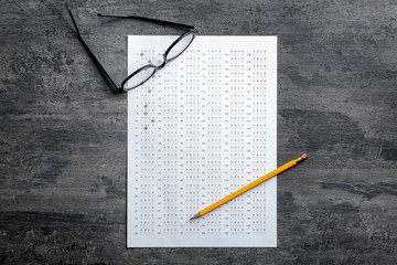 Exam form, pencil and student's eyeglasses on table