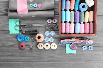 Composition with sewing threads, fabric and accessories on wooden background, top view