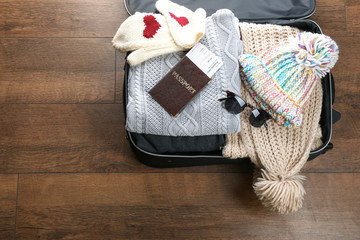Open suitcase with warm clothes and documents on wooden floor. Winter vacation concept